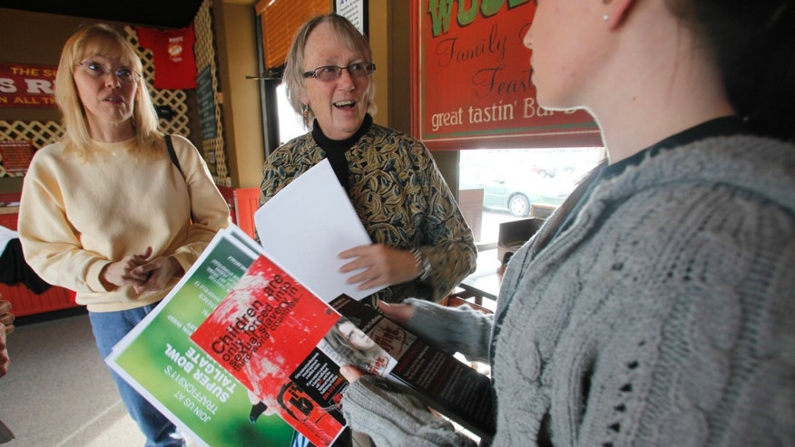 Jan. 27: Anti-sex trade advocates Jackie Edmonds, center, and Mary Thrasher, left, ask restaurant manager Amanda Housley to display anti-sex trafficking awareness literature during an outreach program near the Super Bowl site in Arlington, Texas.