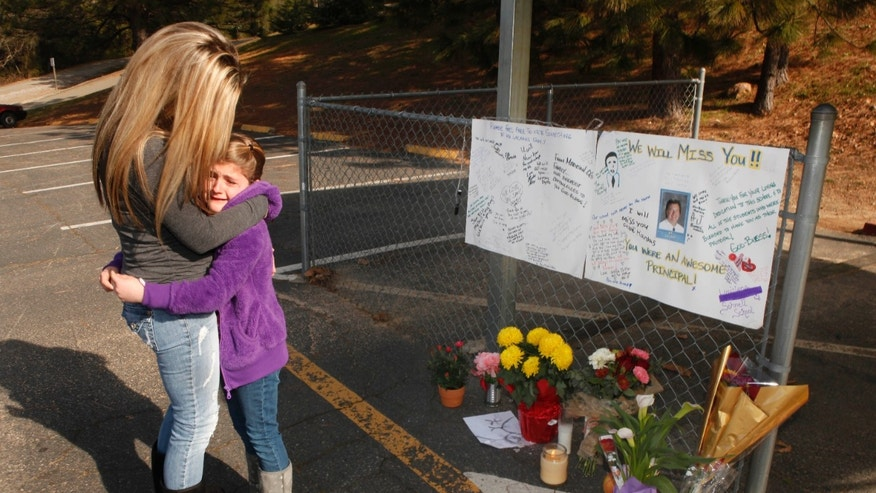 Feb. 3: Lindsay Byers comforts her daughter, Chloe Harbas, 8, after she signed a memorial for Sam LaCara, 50, the principal of the Louisiana Schnell School in Placerville, Calif. who was shot and killed at the school the previous day. The alleged gunman, school janitor John Leubbers, was taken into custody about an hour after the shooting.