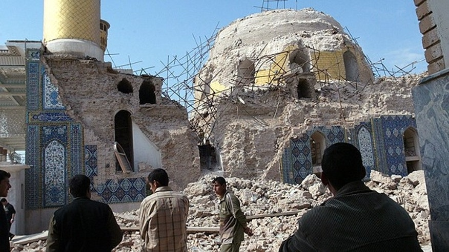 In this Feb. 22, 2006 file photo, Iraqis gather at the ruins of the al-Askari mosque in Samarra, Iraq.