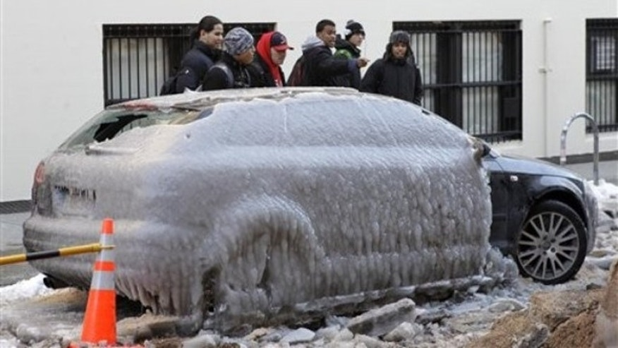Jan. 24: Pedestrians gawk at Pete Helfer's car, frozen under a sheet of ice on a New York City street after a water pipe broke nearby (AP).