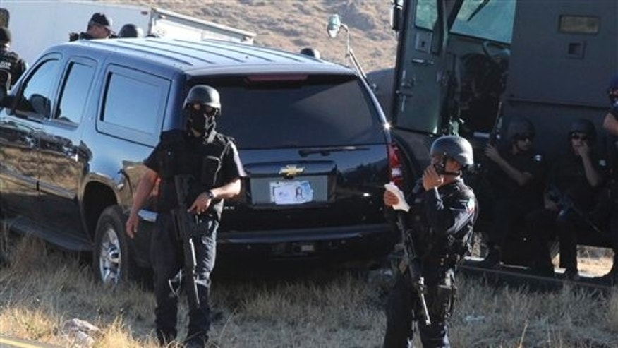 Feb. 15: Mexican federal police guard a U.S. Embassy vehicle after it came under attack by unknown gunmen on Highway 57 between Mexico City and Monterrey, near the town of Santa Maria Del Rio, San Luis Potosi state, Mexico. A U.S. Immigration and Customs Enforcement agent was killed and another wounded in the attack.  (AP)