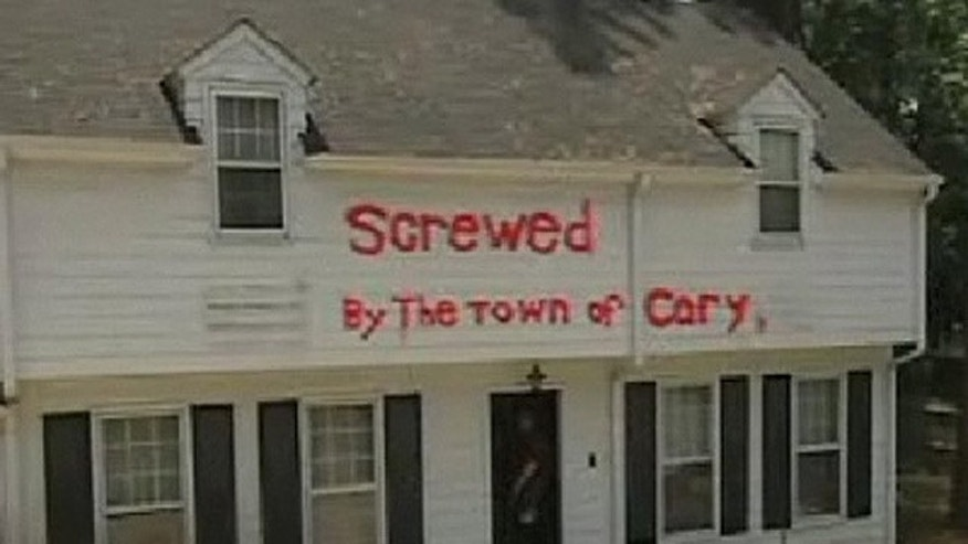 "In 2009, David Bowden sued when town officials tried to fine him for a sign in his yard that read ""Screwed by the town of Cary"" painted in neon orange. Bowden claims his home was damaged by runoff that he blames on local road construction. (MyFox8.com)"