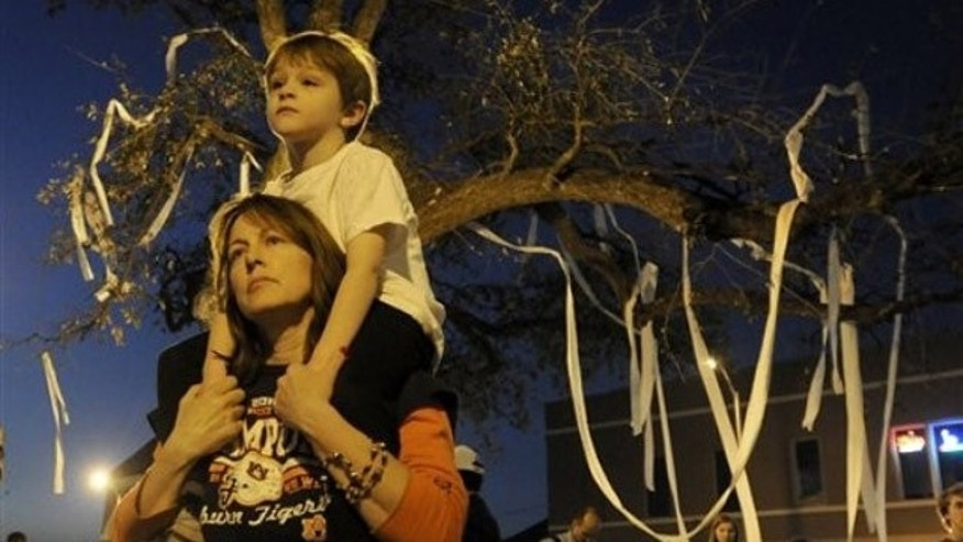 Feb. 16: Toni Rich holds her son Gabriel, as students and supporters gather to pay tribute to live oaks at Toomer's Corner on the campus of Auburn University after word spread that the trees were poisoned recently. Toomer's Corner has long been a site where Auburn fans celebrate big wins, including the football national championship on Jan. 10 (AP).