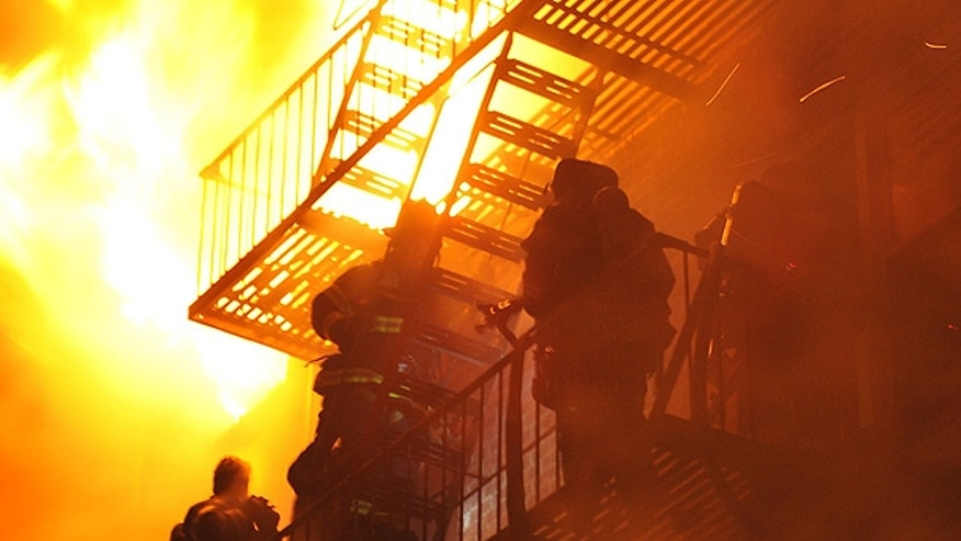 Feb. 19: Firefighters stand on the fire escape as winds whip flames from a five-alarm fire in Brooklyn, New York.