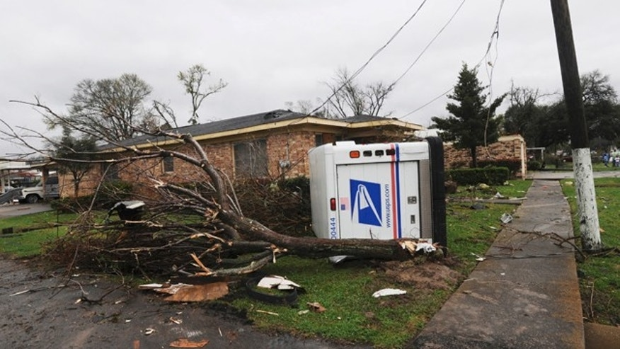 A U.S. Postal truck lies on its side in the yard of a home in Rayne, La., after a suspected tornado hit the area injuring at least nine people, leveling homes and causing natural gas leaks that prompted evacuations on Saturday, March 5, 2011.