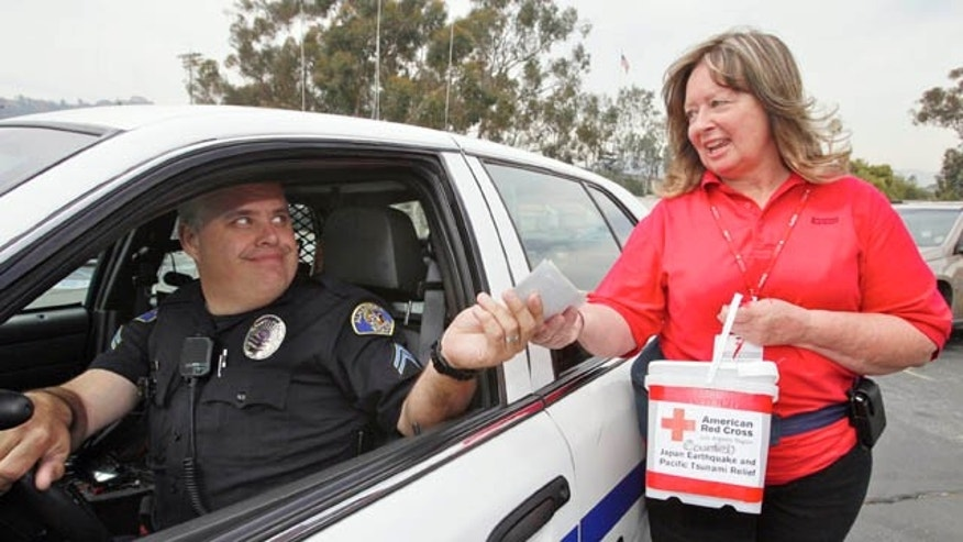 March 14: Alhambra Police officer Kevin Lang drives in to drop checks and cash donated by his station police officers to American Red Cross volunteer Cathy Sproule for the Japan Earthquake and Pacific Tsunami Relief Fund at the Rose Bowl in Pasadena, Calif. (AP)