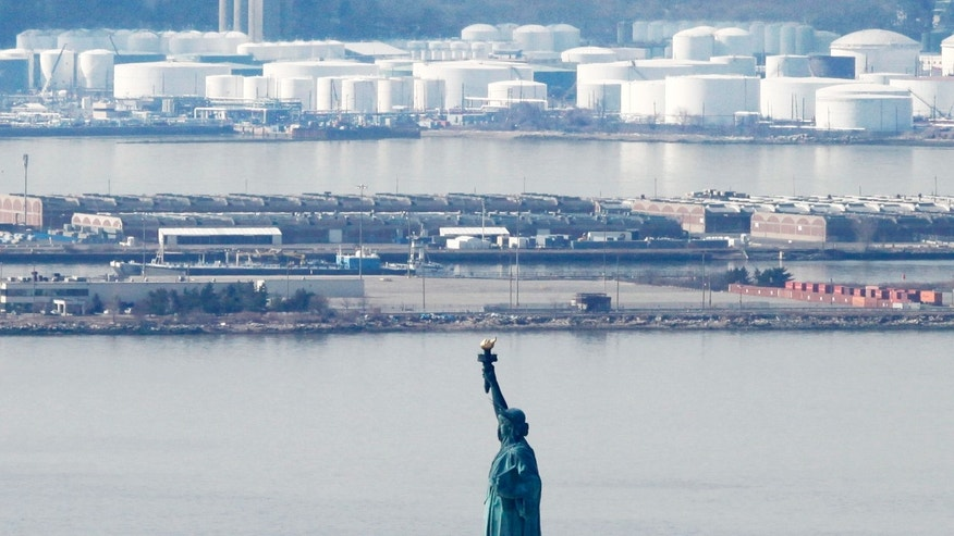 March 15: The Statue of Liberty stands in New York Harbor with an oil storage facility behind it in New York. Oil prices fell with concerns over Japan's economy, but they rebounded March 16 as demand for energy was high amid world crises.