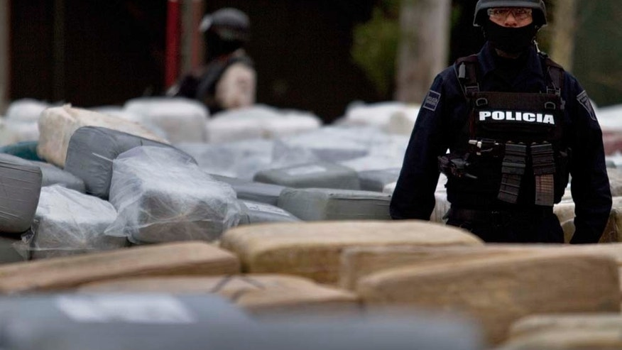 FILE: A Mexican police officer guards packages of seized marijuana during a presentation for the media in Tijuana, Mexico. American teenagers are being recruited by Mexican drug cartels to carry drugs across the U.S.-Mexico border. (AP Photo/Guillermo Arias)