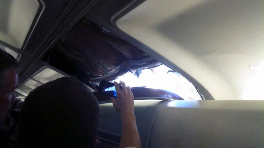 April 1: In this photo provided by passenger Brenda Reese, unidentified passengers take photos with cell phones of an apparent hole in the cabin on a Southwest Airlines aircraft in Yuma, Ariz. Authorities say the flight from Phoenix to Sacramento, Calif., was diverted to Yuma due to rapid decompression in the plane.  FAA spokesman Ian Gregor says the cause of the decompression isn't immediately known. But passengers aboard the plane say there was a hole in the cabin and that forced an emergency landing. (AP)