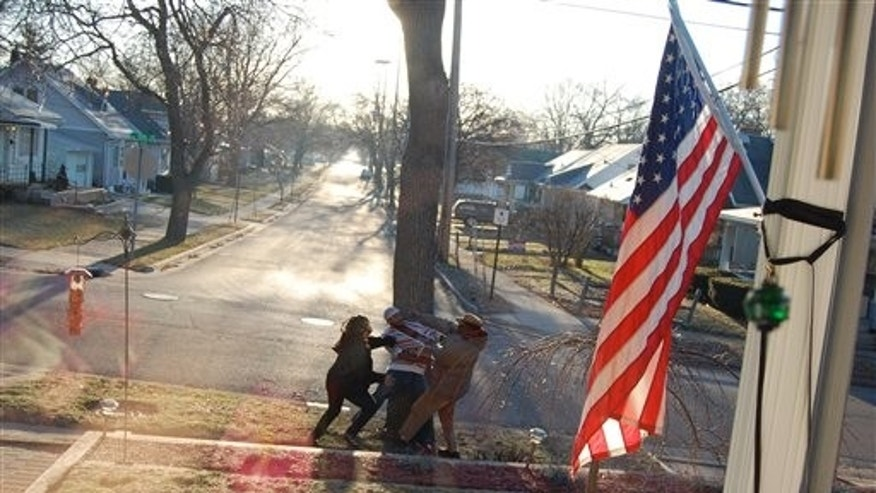In this Thursday, March 31 photo taken by an unidentified witness, crossing guard James Thompson, 73, is attacked by two suspects in Lansing, Michigan.