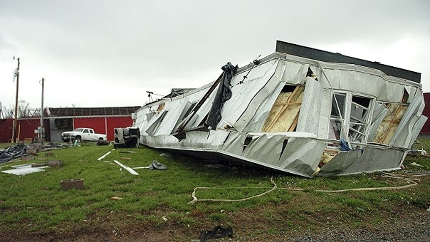 April 4: The mobile home of Eric Williams came to rest on its roof after severe storms ripped through the area near LaCenter, Ky.