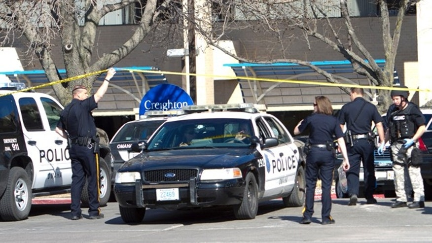 April 6, 2011: Police officers and vehicles work the scene in front of the Creighton University Medical Center, in Omaha, Neb., following a shooting inside the hospital. Omaha police have arrested a suspect.