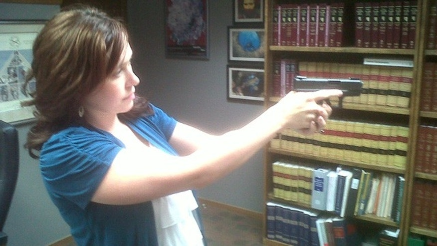 Amanda Collins, 25, shows a 9-mm Glock that she is permitted to carry and use for self defense.