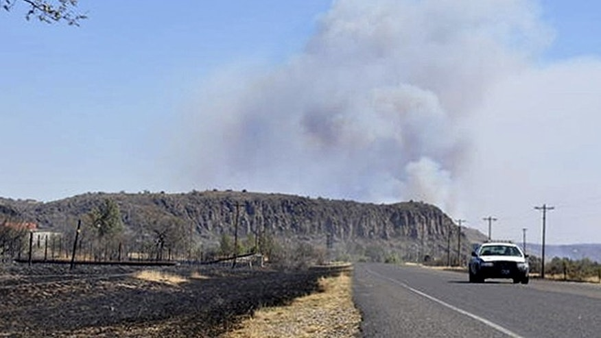April 10: With smoke rising from a wildfire in the background, a state trooper drives along a road in Fort Davis, Texas.