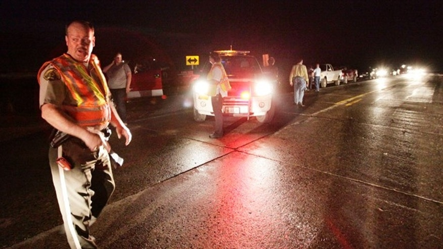 April 9, 2011: A Sheriff's deputy blocks off the intersection of Highways 141 and 175 preventing people from entering Mapleton, Iowa after a tornado struck the town.A