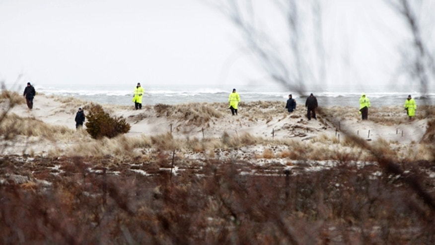 April 5, 2011: In this file photo emergency personnel search the dunes and scrub near the ocean, across the road from where eight bodies where found, near Oak Beach, N.Y.