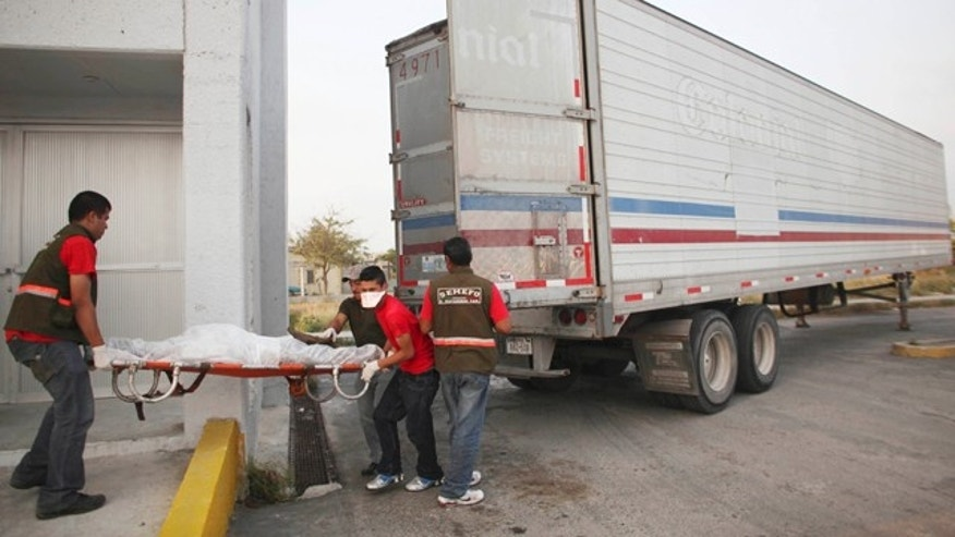 April 7 2011: Morgue workers remove a body found in a mass grave from a refrigerated truck in Matamoros, northern Mexico.