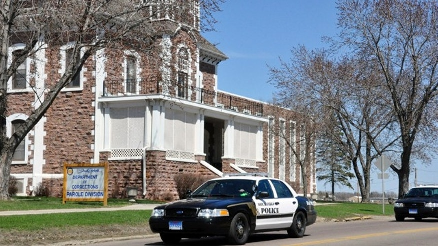 April 12, 2011: Two police cruisers leave the South Dakota State Penitentiary where a guard was shot and killed during a failed escape attempt in Sioux Falls, S.D. The two suspects in the case were apprehended.