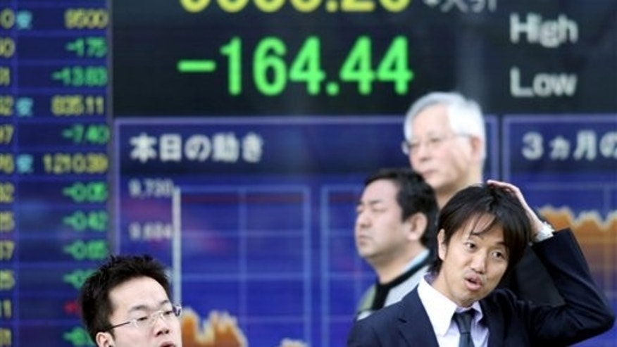 April 12: People in front of an electronic stock board at a securities firm in Tokyo.