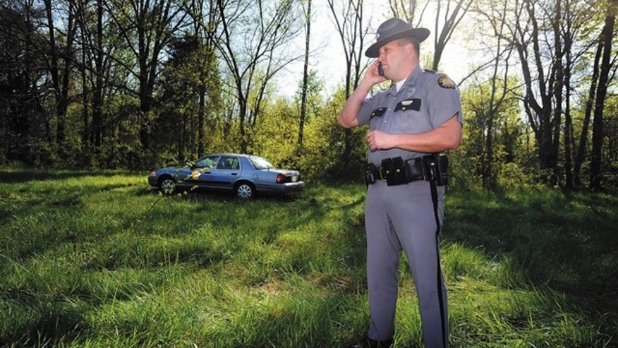 April 14: Kentucky State Police Trooper Jonathan M. Biven talks on his cellphone in a wooded area off U.S. 68-Ky. 80 in  Oakland, Ky., where police found the body of Jamie Stice, 21, of Bowling Green.