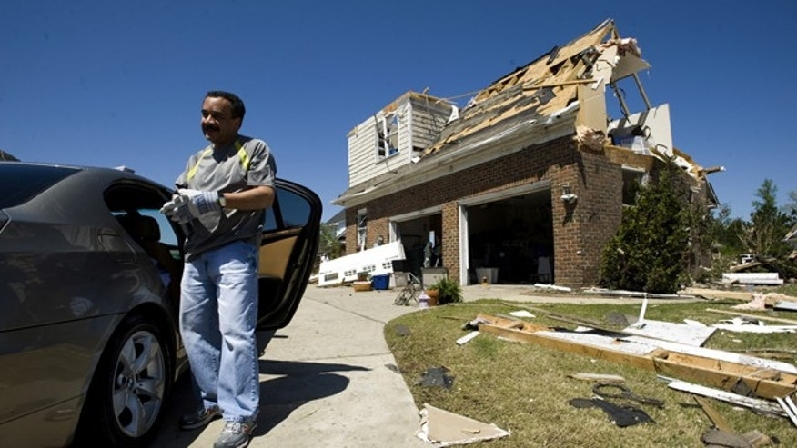 April 17: Hector Diodonet, President of the Home Owner Association of the Fairfield Farms subdivision in Fayetteville, NC talks with neighbors while cleaning up his home.