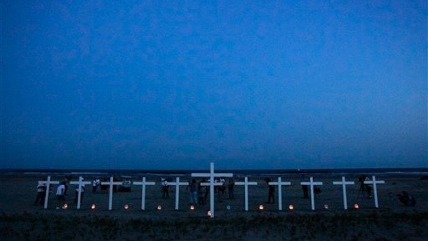 April 20: People gather near crosses -- 11 for the workers who died in the Deepwater Horizon oil rig explosion and one for the Gulf of Mexico on a beach in Grand Isle, La.