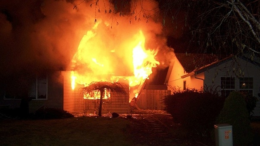 April 24: In this photo provided by Kathy Larsen via The Columbian, flames engulf a house in Vancouver, Wash.