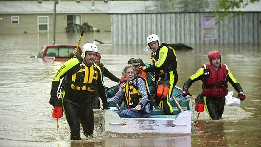 April 25: Residents of Oak Glen Residential Community are assisted by rescue personell as rising waters from a nearby creek forced them to evacuate their homes in Johnson, Ark.