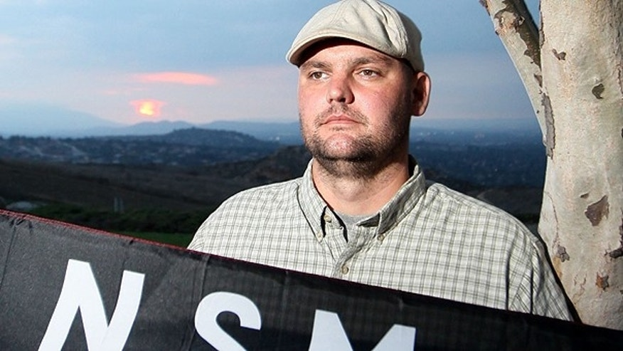 In this file photo taken Friday, Oct. 22, 2010, Jeff Hall holds a Neo Nazi flag while standing at Sycamore Highlands Park near his home in Riverside, Calif.