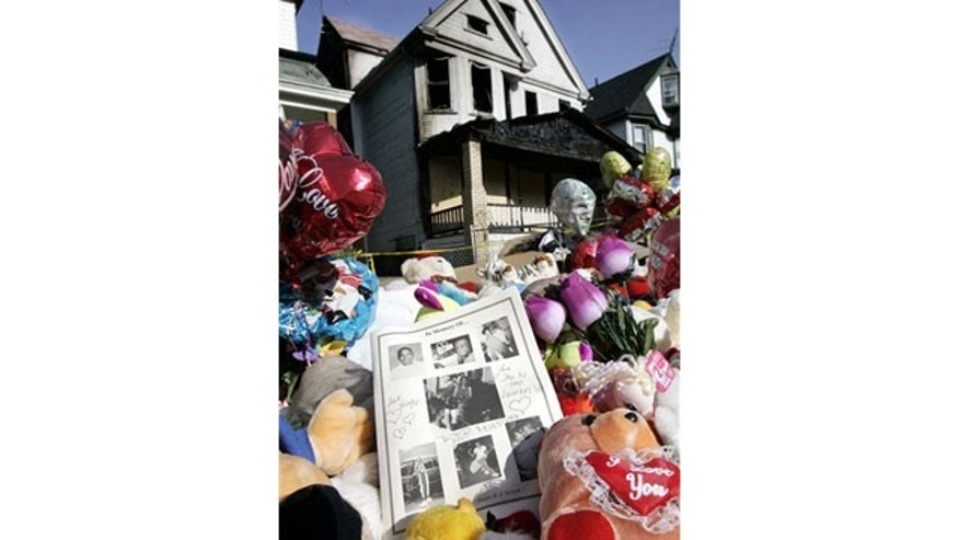 June 2005: Pictures of the fire victims rest on stuffed animals in front of the burned-out house in Cleveland, in which nine people died.