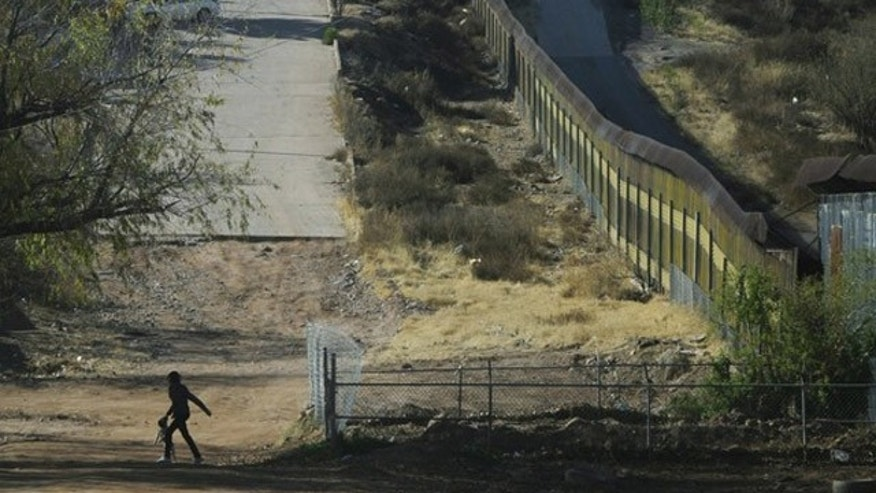 Jan. 6: A woman with a dog walks near the border fence between Mexico and the United States in Nogales.