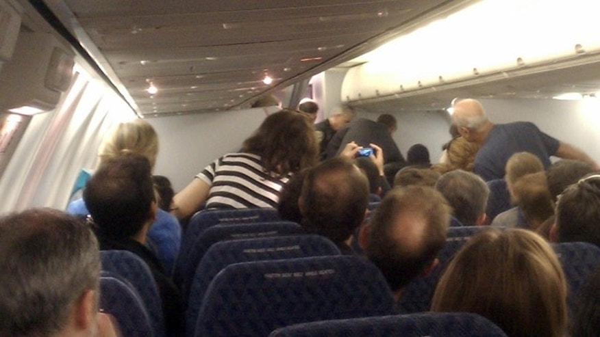 May 8: In this image captured by citizen journalist Andrew Wai, passengers, top right, subdue a man identified as Rageh Almurisi (not seen) on board an American Airlines flight headed to San Francisco