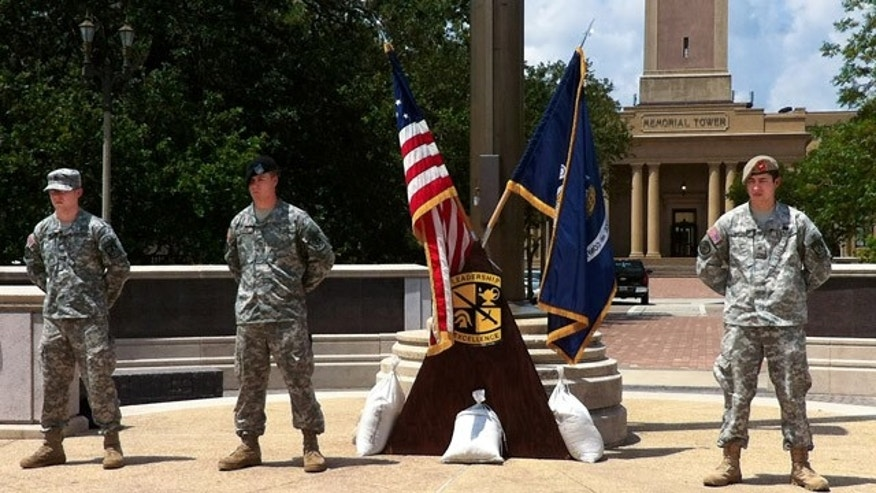 ROTC members at LSU stand next to the flagpole at the school's war memorial.