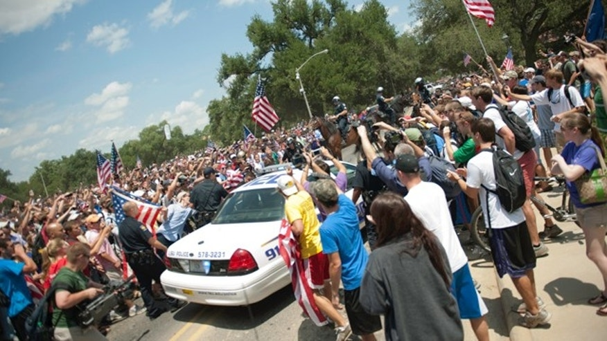 May 11, 2011: Benjamin Haas, a communication studies graduate student at LSU, gets escorted off campus in a police cruiser after protesters surrounded him during a flag-burning protest.
