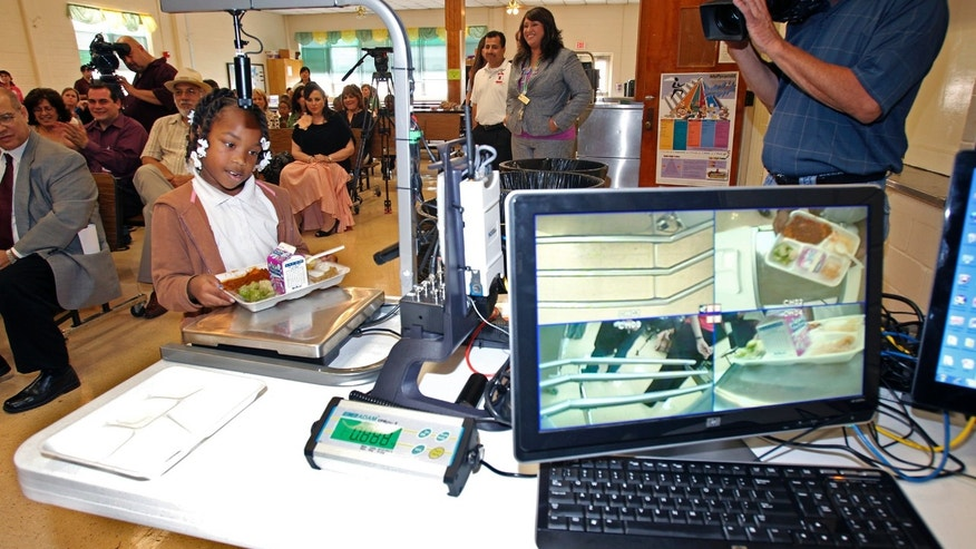 May 11: Third grader Alexis Brooks places her plate on the return tray as digital food analysis equipment is demonstrated at White Elementary in San Antonio.