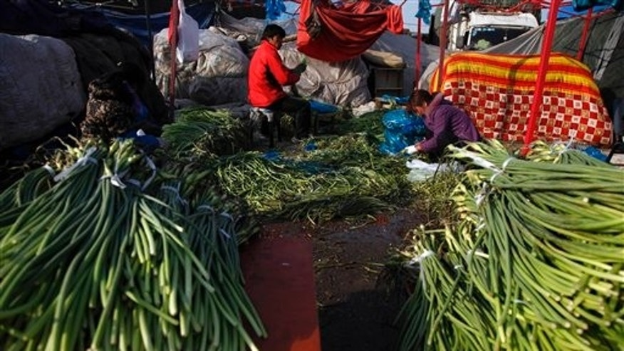 March 16: Vendors clean vegetables at a wholesale market in Beijing, China. In the U.S. the costs of corn, wheat, cotton and other commodities have jumped due to strong global demand.