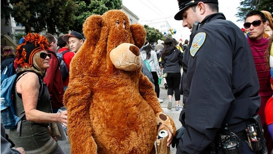 May 15: Police officer Mike Horan stops a bear with a beer and tells him to throw it away, during the Bay to Breakers race.