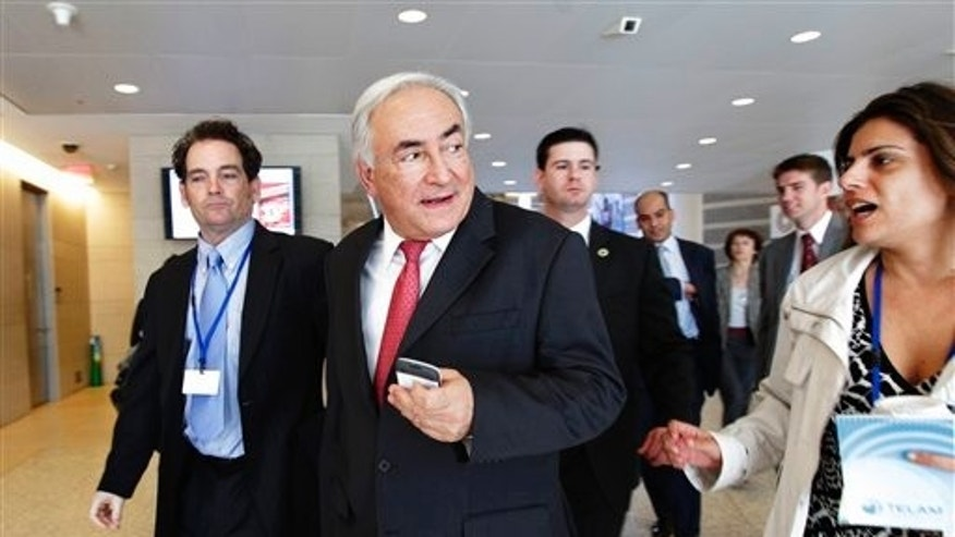 In this April 15, 2011, photo, International Monetary Fund Managing Director Dominique Strauss-Kahn, center, walks to a meeting of the G-20 finance ministers and central bank governors at  the 2011 Spring Meetings of the IMF and World Bank in Washington. (AP)