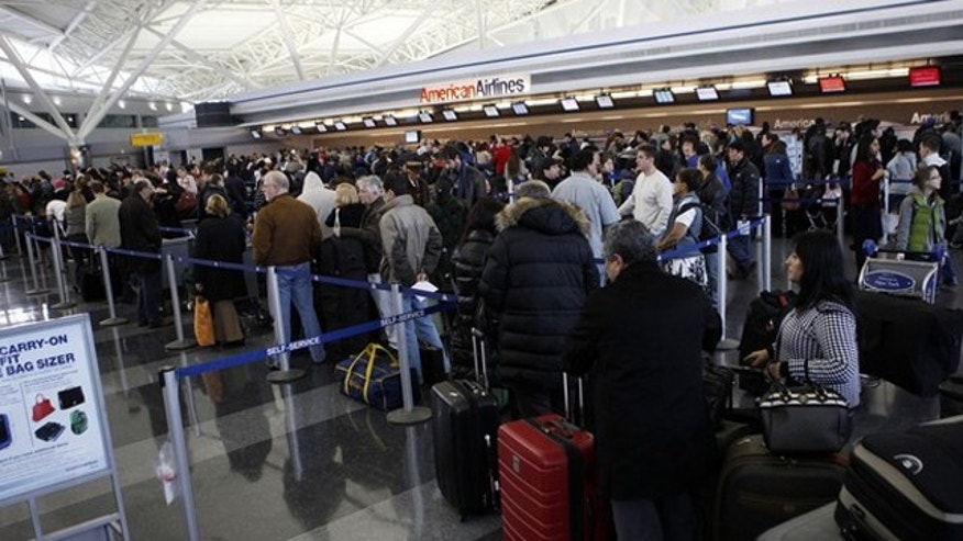Passengers wait in line for ticketing at the John F. Kennedy International Airport as the airport reopened after being closed due to heavy snowfall in New York, January 27, 2011. REUTERS/Jessica Rinaldi (UNITED STATES - Tags: ENVIRONMENT TRANSPORT)