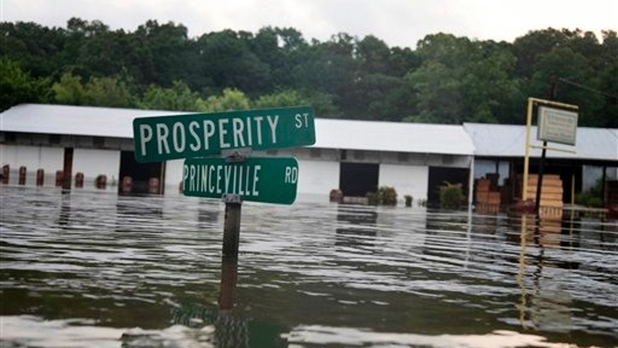 May 20: A street sign is seen in floodwaters from the rising Mississippi River in St. Francisville, La., where a dozen homes and businesses, and several camps, were flooded. Residents were leaving in the face of a mandatory evacuation order set to kick in on Saturday as Mississippi River water flowing through the Morganza spillway is expected to reach communities in the Atchafalaya Basin. (AP)