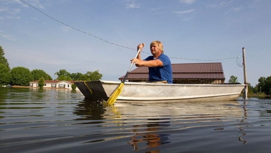 Chris Lynn paddles his boat through floodwaters surrounding his home after making his morning trip to check the water levels at his property in Vicksburg, Miss. on Saturday, May 21, 2011. Lynn said that the Mississippi River floodwater had receded several inches from Friday.
