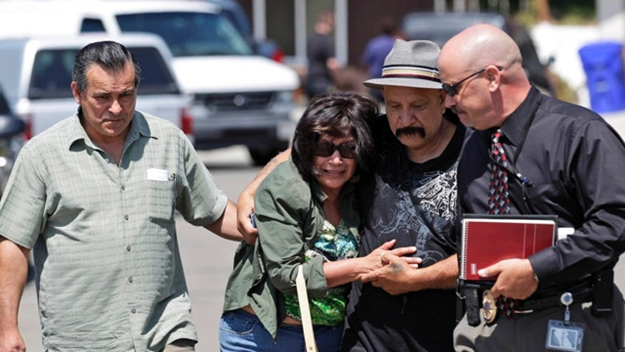 May 24: Relatives of the drowning victims walk away from the scene alongside a detective, right, in San Diego.