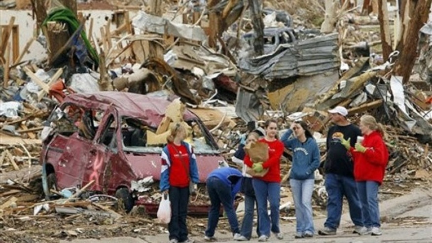 May 26: Volunteers stop to look at debris as they walk to their work site in Joplin, Mo. A tornado tore through much of the city Sunday, wiping out neighborhoods and killing at least 123 people (AP).