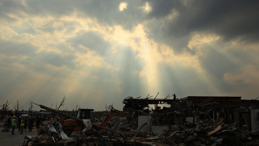A search and rescue team surveys the area from atop the rubble of a destroyed building in Joplin, Mo. on Saturday, May 28, 2011. An EF-5 tornado tore through much of the city Sunday, damaging a hospital and hundreds of homes and businesses and killing at least 139 people.
