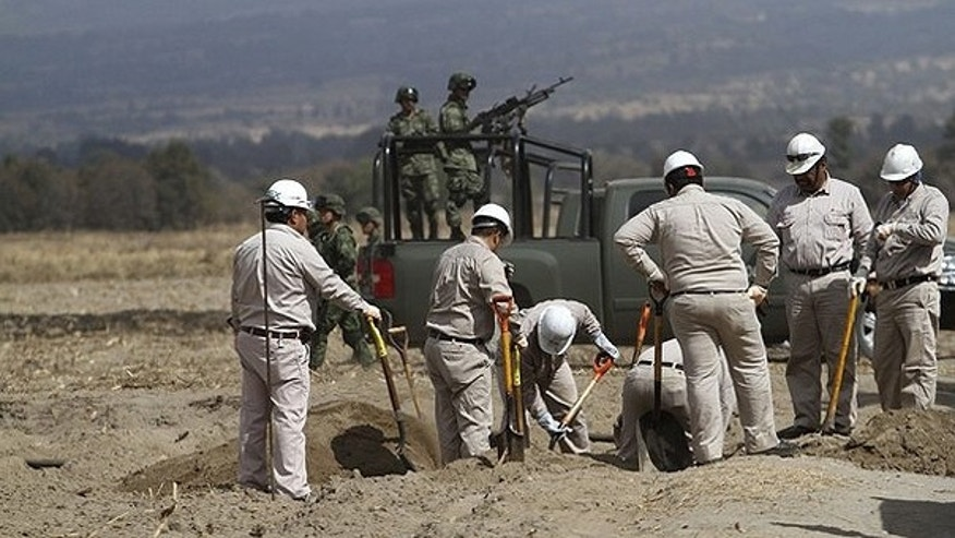 Feb. 4: Workers from the state-owned oil company Pemex uncover an illegal connection to an oil pipeline as soldiers stand guard in Amozoc. Pemex detects dozens of illegal tabs on their pipelines every month.