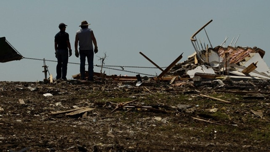 May 29: Scott Vorhees, left, and his friend Doc Murphy watch while a volunteer with a tractor uses a chain to pull down what remained of Vorhees' devastated Joplin, Mo., home.