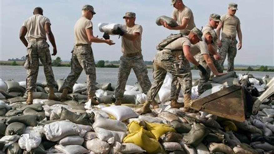 June 2: South Dakota army national guardsmen help sandbag in Dakota Dunes, S.D.