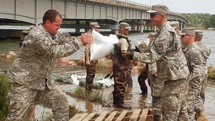 June 2: South Dakota National Guard members from Watertown, S.D. stack sandbags to prevent floodwaters from the rising Missouri River from reaching an electrical box in Ft. Pierre, S.D.