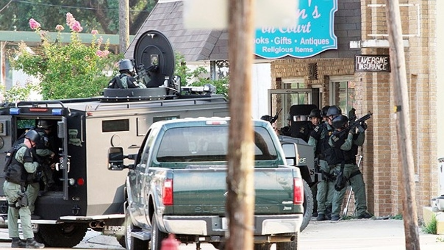 June 7: Louisiana State Police SWAT team members respond to the scene of a double-homicide at an insurance agency on West Main Street in downtown Ville Platte, La.