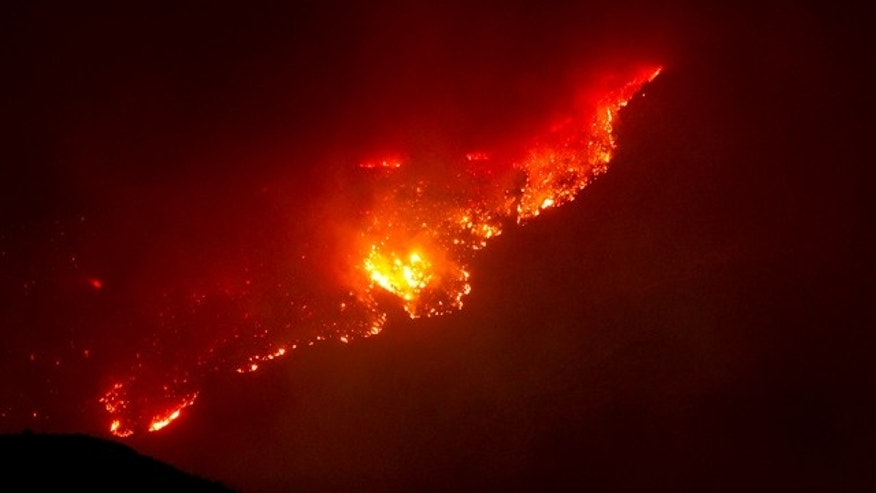 June 8: A mountain top glows from the Horseshoe Two fire near Paradise and Portal, Ariz.